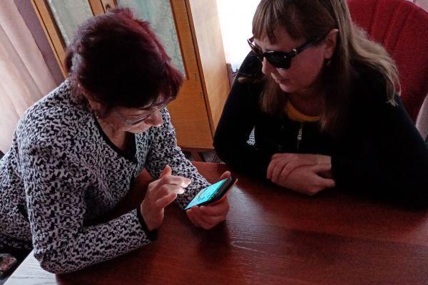 Вялых В.А. обучает пользоваться сенсорным телефоном Хилько В.И.
