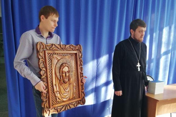 Служитель собора дарит икону Иисуса Христа