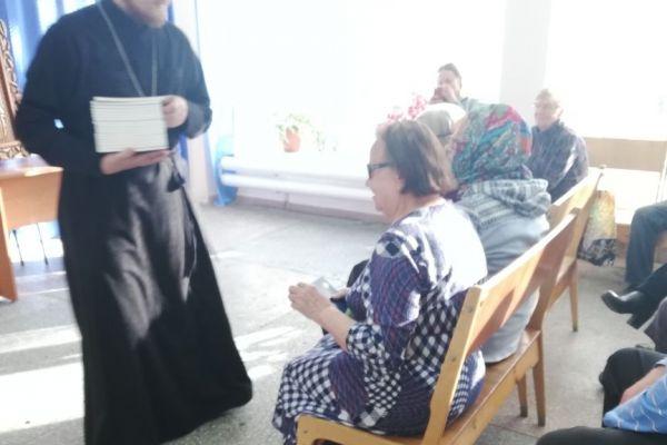 Служитель собора вручает книги
