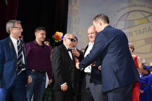 Лидер КПРФ  вручает награду