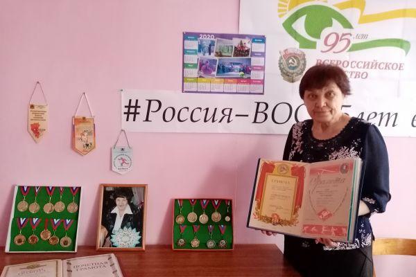 Любовь Ивановна представляет  выставку наград.